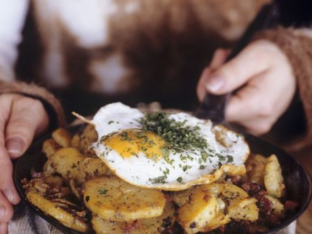 Onion And Bacon Fried Potatoes Topped With Fried Eggs