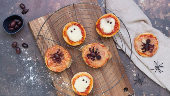 Mini pizzas with mozzarella and olives on a cake rack