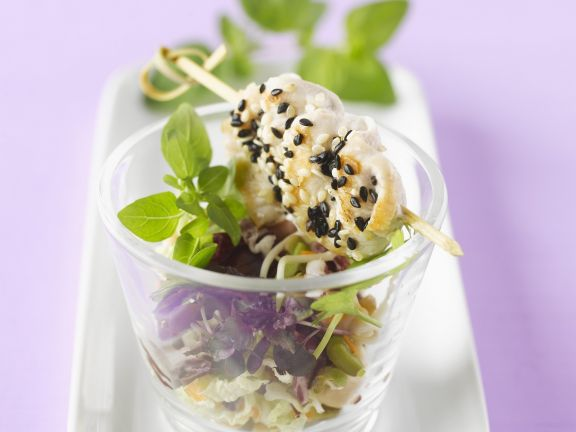 Chicken and Sesame Seed Skewers on Salad