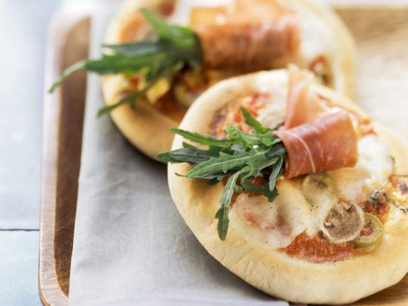 Small Pizzas with Arugula and Ham